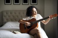 ベッドルームでギターを弾く女性