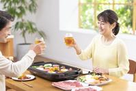 生ビールで乾杯し焼肉を食べる中高年夫婦