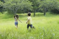 野原を走り回るハーフの男の子と女の子の後ろ姿