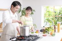 キッチンで料理する中高年夫婦