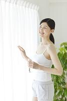 ミネラルウォーターを持ち窓辺に立つ若い日本人女性