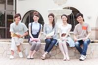 噴水の前に座っている大学生