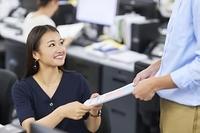 笑顔で書類を受け取る日本人ビジネスウーマン