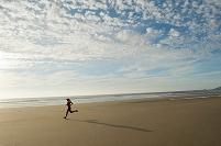 ビーチでジョギングする若い外国人女性
