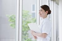 廊下にいる笑顔の若い日本人女性看護師