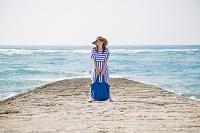 海岸でバッグを持って立つ日本人女性