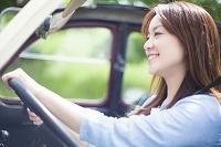 運転席に座りハンドルを握る笑顔の日本人女性