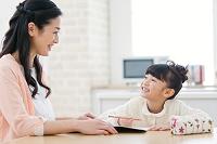勉強をする娘と見守る母親