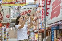 新世界をスマホで撮影する日本人女性