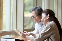 タブレットを見ている日本人シニア夫婦