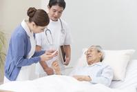 在宅医療する医者と看護師とシニア男性患者