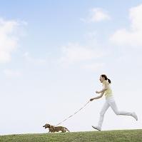 芝生を走る日本人女性と犬