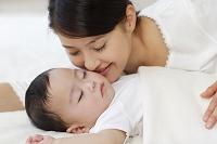 眠る赤ちゃんと見守るお母さん