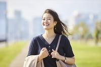 笑顔で通勤をする日本人女性