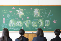 卒業のメッセージの書かれた黒板と学生の後姿