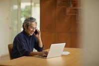 パソコンを操作しながら電話をする日本人男性