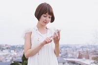 携帯電話でメールをする女性