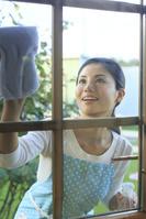 窓ガラスを磨く日本人女性