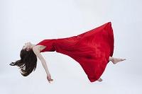 宙に浮く赤いドレスの女性