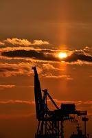 夕日の港とコンテナクレーン