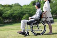 車椅子に乗る中高年男性と押して歩く中高年女性