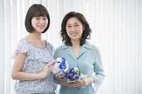 花のブーケとプレゼントを持つ母と娘