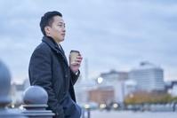 休憩する日本人ビジネスマンと冬の都市