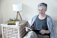 ベッドで本を読むミドル男性
