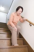 階段で膝を押さえる年配の日本人女性