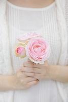 バラの花を持つ若い女性の手