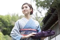小包を持って歩く着物の日本人女性