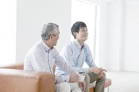ソファに座る笑顔の父親と息子