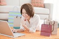 ノートパソコンを操作する日本人女性と紙袋