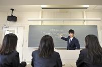 机に座る女子と黒板の前に立つ男子