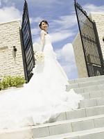 教会のエントランスに立つ花嫁と青空