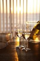 夕陽に輝くワイングラスとワインクーラー