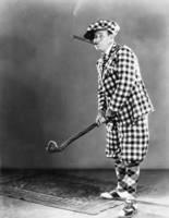 ニッカポッカ姿でゴルフをする男性