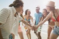 浜辺で円陣を組む若者たち