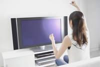 テレビを見ながら応援する女性