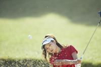 バンカーショットを打つ女子ゴルフ選手