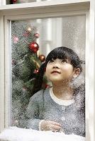 クリスマスを過ごす窓辺から遠くを見る女の子