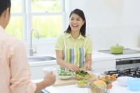 明るいキッチンで料理をする妻とお茶を飲む夫