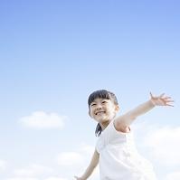 青空の下で手を広げる日本人の女の子