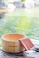 新緑の露天温泉に置かれた桶と手ぬぐい