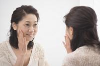 鏡の前で化粧前の顔を見る中高年日本人女性