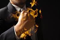 ガッツポーズするビジネスマンと炎