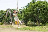 公園の遊具で遊ぶ元気な女の子
