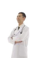 腕を組み微笑む医師