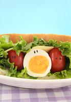 顔のあるかわいいゆで卵とミニトマトとレタス