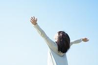 空を見上げて手を伸ばす日本人女性